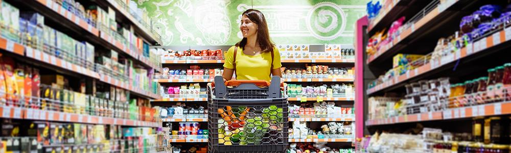 Egy nő bevásárlókocsival a boltban, teli polcok, nincsenek kiürült raktárkészletek